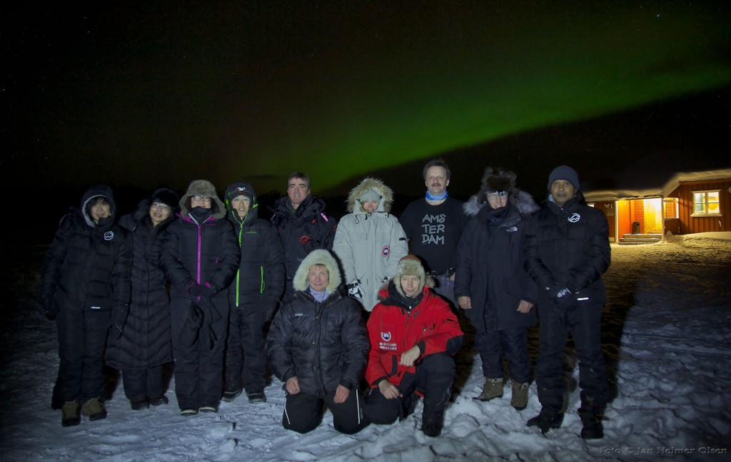 Group photo with Aurora in Background, guests from Hong Kong, UK, India and Norway.