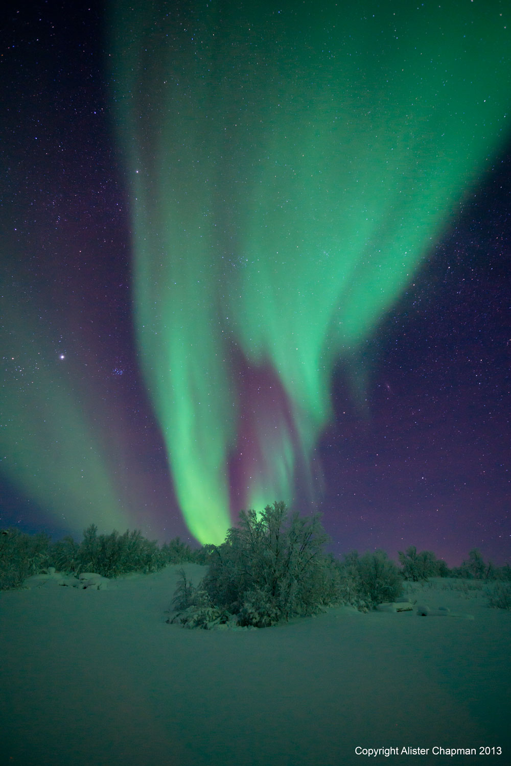 Like green flames or smoke the Aurora streaks into the sky.
