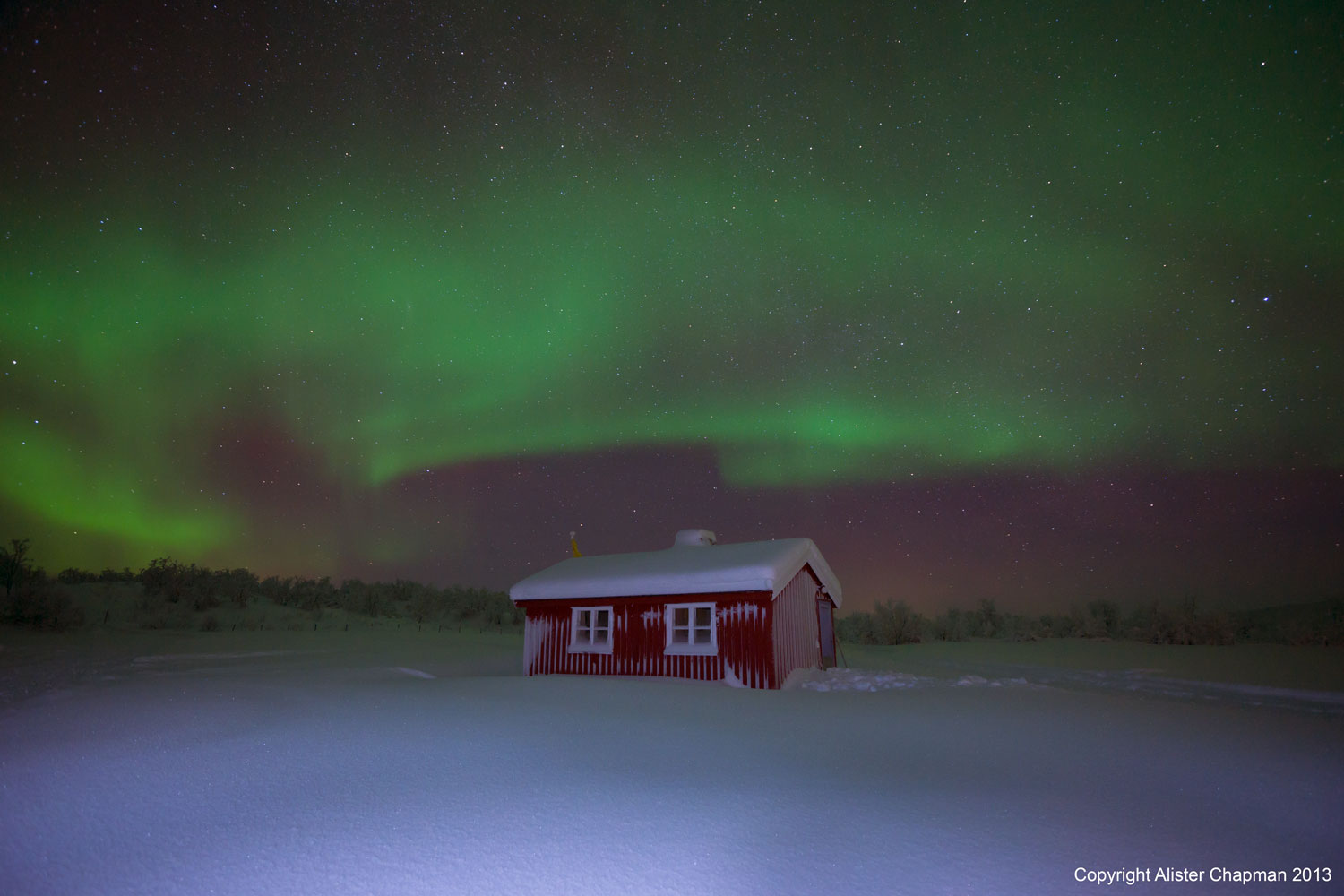 The Aurora shines bright above one of the cabins.