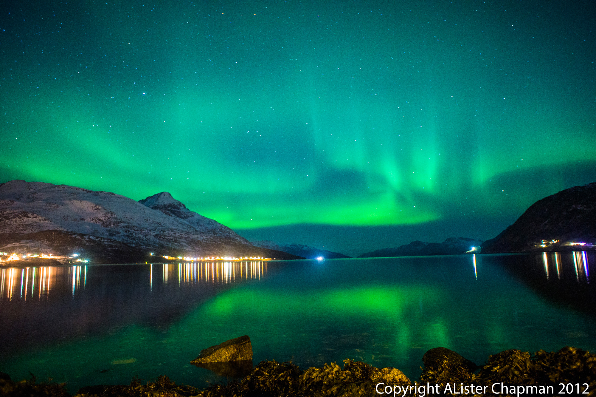 The Northern Lights reflected from the cold waters of a Fjord near Tromso.